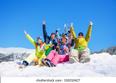 Group of four snowboarders friends sitting on the snow in the