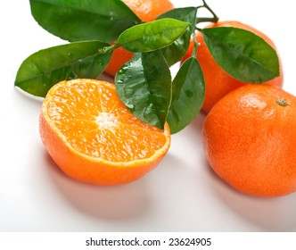 a group of four tangerines with leaves, one cut in half
