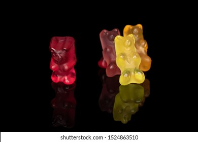 Group of four whole gummy bear isolated on black glass