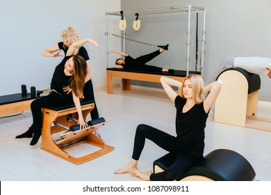 Group of four women and man in black sportswear working out with different pilates equipment on eco modrn pilates studio.