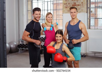 Group of four young adult male and female friends posing with exercise gear at small athletic fitness gym