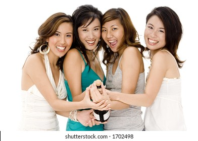 A group of four young asian women enjoying opening a bottle of champagne
