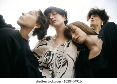Group of four young beautiful models in desert. Black clothes, high fashion looks, conceptual hairstyle . Metal constructions. Sand. Melancholy mood. Minimalism and japanese design. Without retouch
