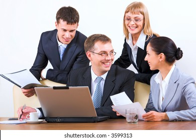 Group of four young businesspeople discussing different questions holding documents gathered together around the table with the laptop, drinks and papers on it