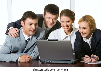 Group of four young businesspeople gathered together around the laptop discussing interesting question