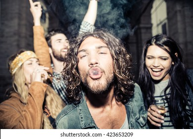 Group of four young friends having party, smoking and drinking alcohol - Best friends clubbing in the night, frontal flash to give realism to the scene