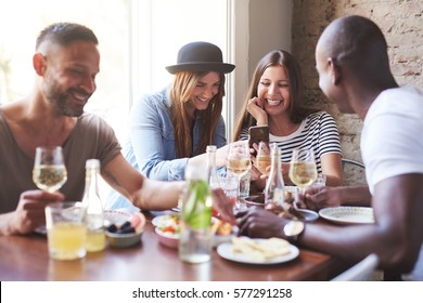 Group of four young friends having dinner in cozy cafe while women sharing new on phone.