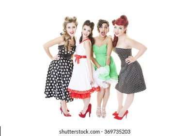 A group of four young girls dressed in Rockabilly, pinup dresses. Shot on white background.