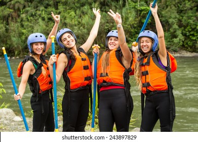 Group Of Four Young Ladies Prepared To Go White Water Rafting Wearing Specific Equipment