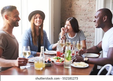 Group of four young people sitting at table dining and having active conversation.