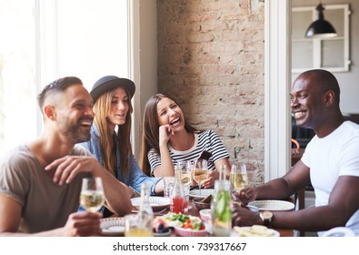 Group of four young people sitting at table in restaurant and having fun while dining.
