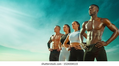 Group of four young sportsmens women and men, fit athletes are standing on the sky background before run. Healthy lifestyle and sport. Friends in black and white sportswear. Fitness concept.