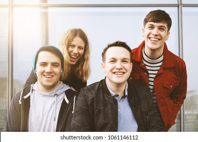 group of four young teenage friends having fun and laughing together, outdoor lifestyle portrait with sun flare