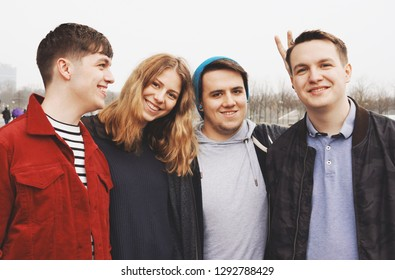 group of four young teenage friends posing arm in arm - fun portrait with bunny ears