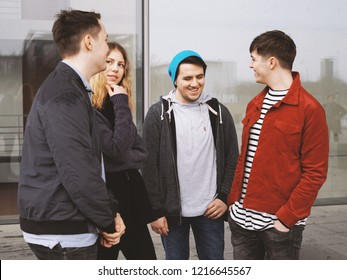group of four young urban teenage friends talking laughing and having fun together - candid real people