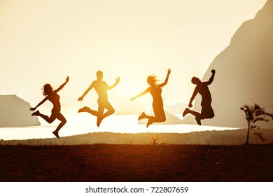 Group of fout happy friends having fun and are jumping on background of sea and islands at sunset or sunrise. Space for text