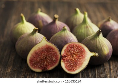 A group of fresh figs with a two sliced pieces in the front.