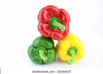 A group of fresh green, yellow and red paprika (Capsicum annuum) on a white background.