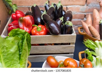 Group of fresh and healthy vegetables. Delicious tomatoes, lettuce, red pepper, parsley and eggplant on a wooden basket. Bio food for cooking.