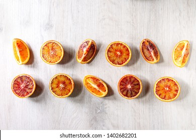 Group of fresh organic Sicilian blood oranges sliced and whole in row over white wooden background. Flat lay, space