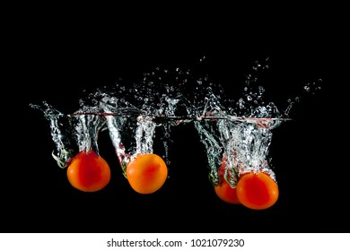 group of fresh red tomatoes in water splash on black background