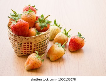 A group of fresh strawberries in a wooden basket