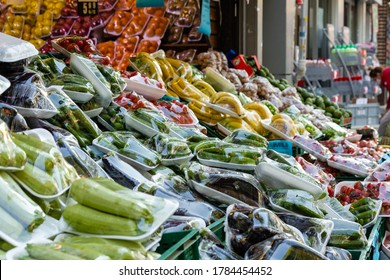 Group of fresh vegetables and fruits packed with stretch film suitable with coronavirus measures on street counter of groceries. Istanbul, Turkey.