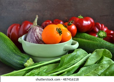A group of fresh vegetables - green spinach, yellow tomatoes,marrow,eggplant, sweet red pepper.