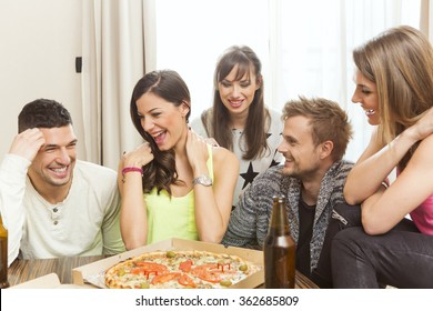 Group of friend having beer and pizza at home