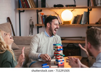 Group of friend playing a jenga at home.