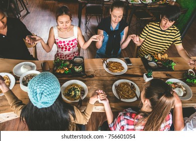 Group of friend pray before having nice food and drinks, enjoying the party and communication, Top view of Family gathering together at home for eating dinner.
