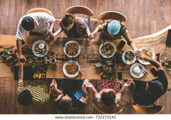 友達のグループは、おいしい食べ物や飲み物を食べる前に祈り、パーティーやコミュニケーションを楽しみ、家族が集まって夕食を食べるトップビューを楽しみます。