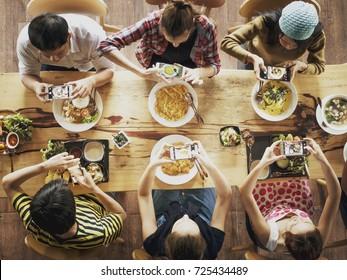 一群朋友在餐厅吃午饭前用手机拍照。顶视图
