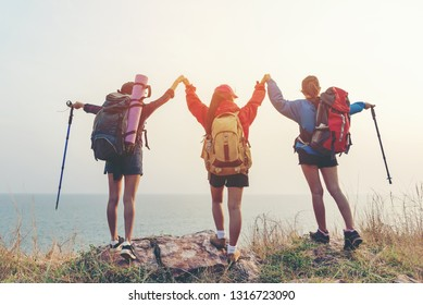 Group friend team asian young women of hikers walking adventure with backpack on a mountain at sunset. Traveler life going trip camping outdoors. Travel and Vacations Concept