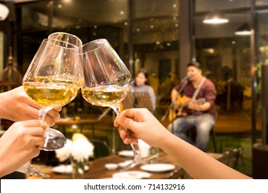 Group of friend toasting with wine for celebration live band in background