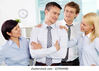 Group of friendly businesspeople adoring their leader in office
