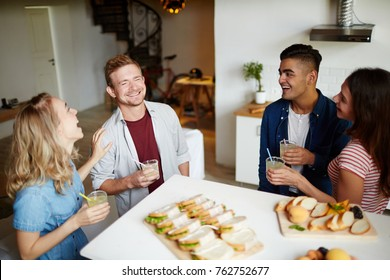 Group of friendly guys and girls laughing while having homemade drinks in the kitchen