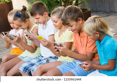 Group of friendly kids playing with mobile phones together outdoors
