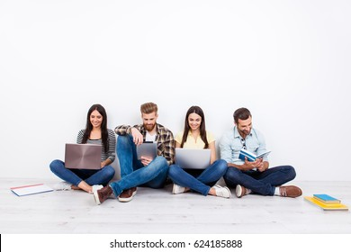 Group of friendly smiling students sitting on the floor and using modern technology for studying
