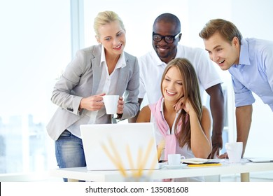 Group of friendly students or businesspeople gathered in front of laptop