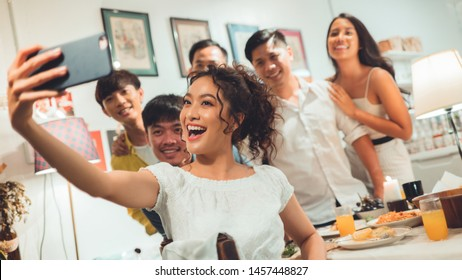 Group friends asian are taking selfies while eating dinner.
