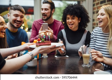 Group of friends are in a bar celebrating on of the women's birthdays. Someone is holding out a dessert with candles which spell 'BDAY' in it.