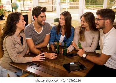 A group of friends at the bar drinking a beer