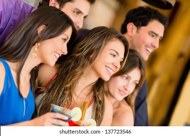 Group of friends at the bar having a drink and smiling