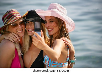 Group of friends at the beach taking photos with a mobile phone