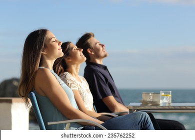 Group of friends breathing fresh air in a restaurant on the beach with the ocean in the background