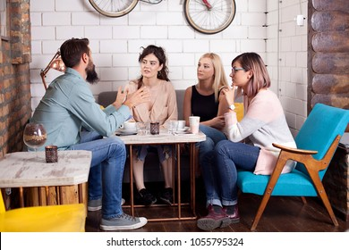 Group of friends in cafe drinking coffee, talking and relaxing