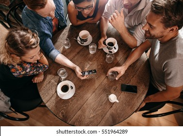 Group of friends at the cafe and looking at smart phone. Man showing something to his friends sitting by.