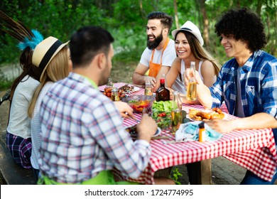 Group of friends camping and having a barbecue in nature