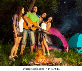 Group of friends camping.They are standing around a camp fire,singing and playing guitar.